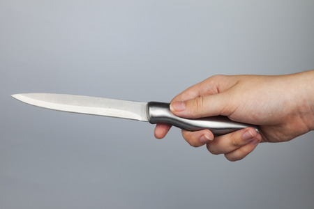 Silver knife in hand over gray background.