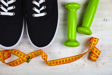 Sneakers, dumbbells and measuring tape on a wooden background. Concept of a healthy lifestyle and sport.