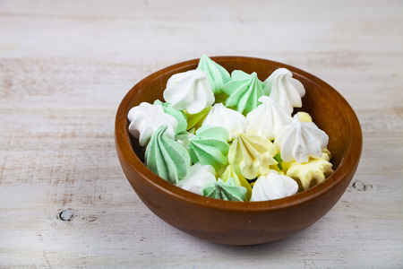 Meringue in white bowl on a wooden background. Delicious dessert. Colorful handmade meringue. Zdjęcie Seryjne