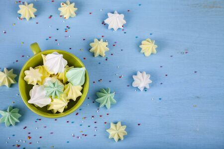 Meringue in a green cup on a blue wooden background, top view. Delicious dessert. Colorful handmade meringue.