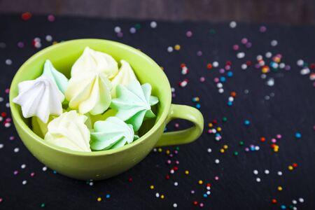 Meringue in a green cup on a dark background. Delicious dessert. Colorful handmade meringue.