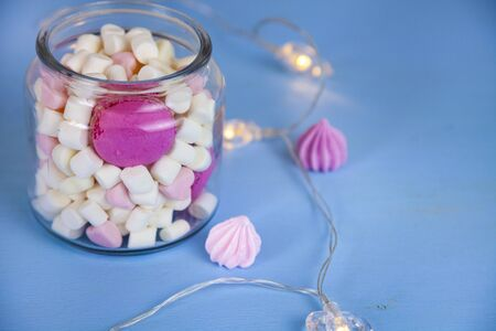 Marshmallow in a glass jar and a garland of hearts. Delicious dessert. 免版税图像