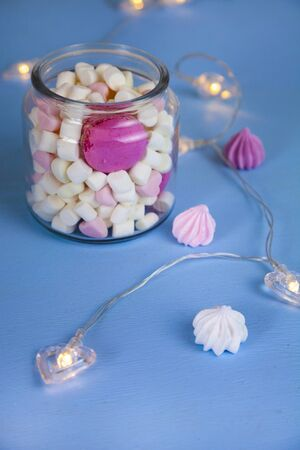 Marshmallow in a glass jar and a garland of hearts. Delicious dessert.