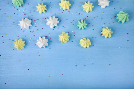 Meringue on a blue wooden background, top view. Delicious dessert. Colorful handmade meringue.