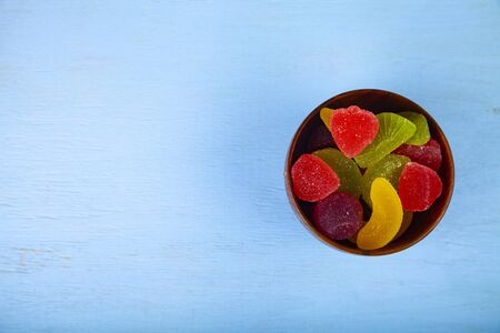 Multicolored marmalade in a bowl on a blue  wooden background. Delicious dessert.
