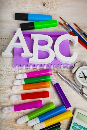 Back to school. Items for the school and letters ABC on a wooden table.