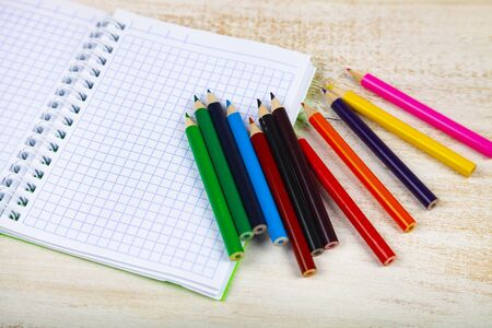 Back to school. Items for the school on a wooden table. Pencils and notebook.