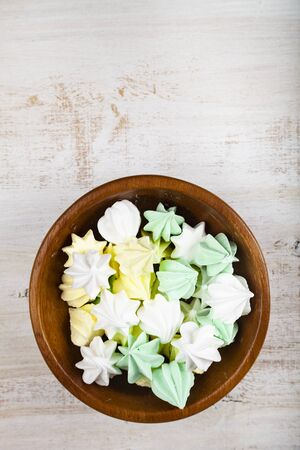 Meringue in a bowl on a wooden background, top view. Delicious dessert. Colorful handmade meringue. Imagens - 128462616