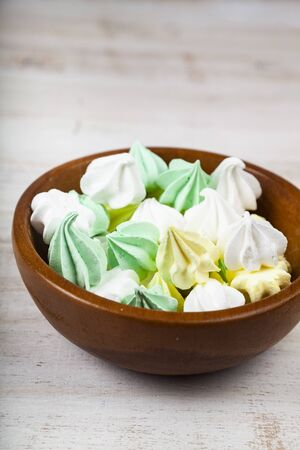 Meringue in a bowl on a wooden background. Delicious dessert. Colorful handmade meringue. Imagens - 128462615