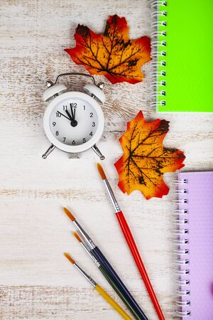 Back to school. Alarm clock, notebooks, brushes and autumn leaves on a wooden table.