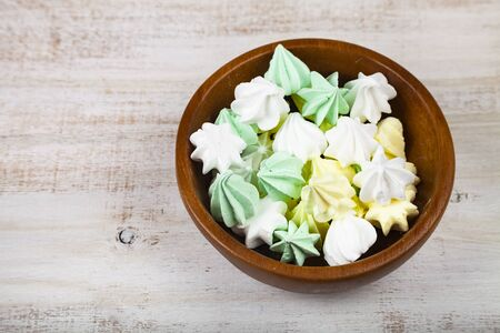Meringue in a bowl on a wooden background, top view. Delicious dessert. Colorful handmade meringue. Imagens - 128462717