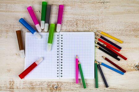 Back to school. Items for the school on a wooden table.Pencils and felt-tip pens on a notebook. Banco de Imagens
