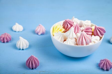 Tasty white and pink meringues on a blue wooden background. Imagens - 129832853