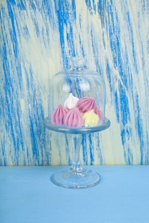 Tasty white and pink meringues on a blue wooden background.