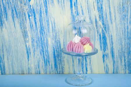 Tasty white and pink meringues on a blue wooden background. Imagens - 129832862