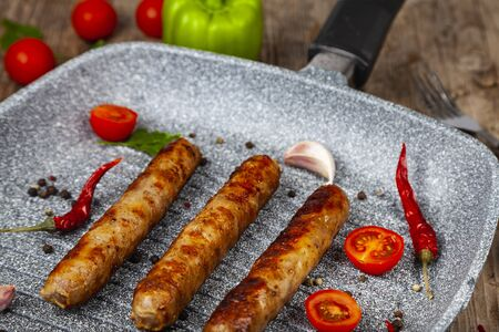Kupaty in a frying pan, vegetables and spices. Sausages grill. Tasty food. Фото со стока