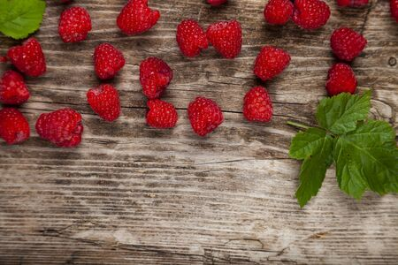 Ripe raspberry on an old wooden table. Delicious berries. Stock Photo