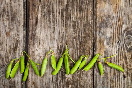 Pea pods on a wooden background. Banque d'images
