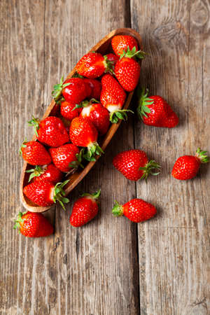Ripe strawberries in a wooden plate on a wooden background. Still life with delicious berries.