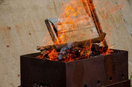 Burning logs in a barbecue grill. Open fire. Burning tree. BBQ preparation. Picnic preparation Archivio Fotografico