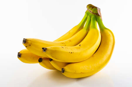 A bunch of ripe yellow fresh bananas on a light background