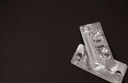 Two empty silver blisters from pills on a dark background