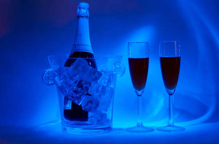 icecubes: Night-time cellebration (bottle in jar with icecubes and two drinks in special light) Stock Photo