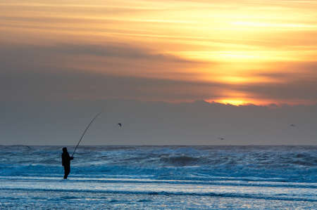 man fishing: A man fishing on the beach at sunset Stock Photo