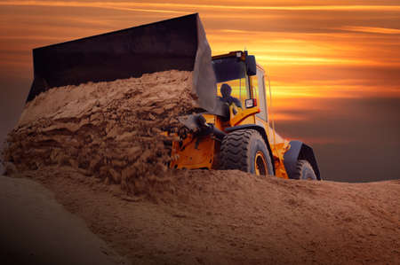 Bulldozer bei der Arbeit mit Sonnenuntergang Hintergrund  Standard-Bild