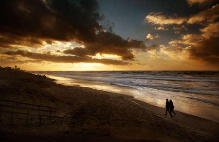 dia noche: Una pareja caminando por la playa en una hermosa noche