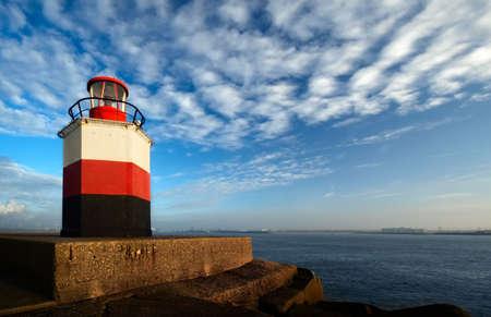 Leuchtturm mit Hafen im Hintergrund Standard-Bild