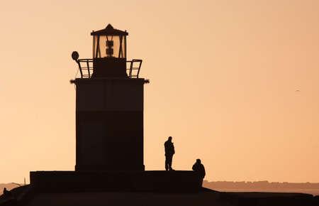Silhouetten von Menschen und ein Leuchtturm