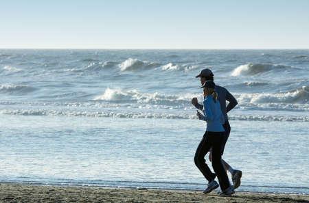 ein paar laufen am Strand entlang