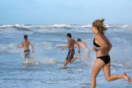 people running into ocean Stock Photo - 765058