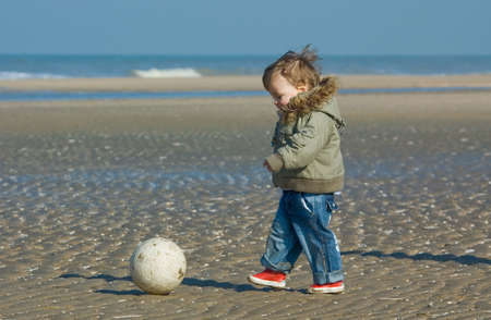 cute boy playing soccer on the beach Stock Photo