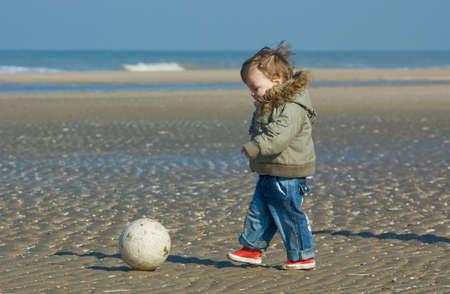 Niedlichen Jungen spielen Fußball am Strand