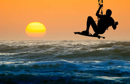 kitesurfen: kite boarder in actie en zonsondergang Stockfoto