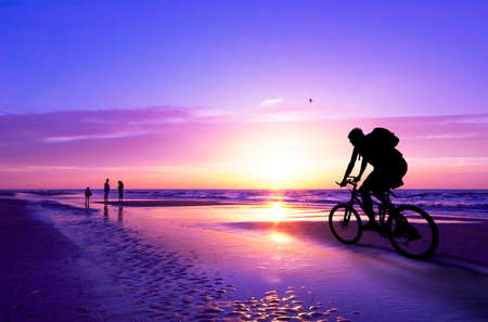 road bike: silhouette of a mountain biker on beach and sunset