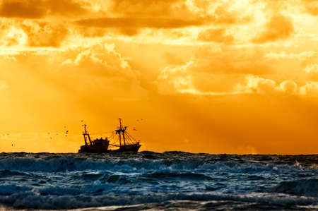 redes de pesca: barco de pesca en el mar con la puesta de sol