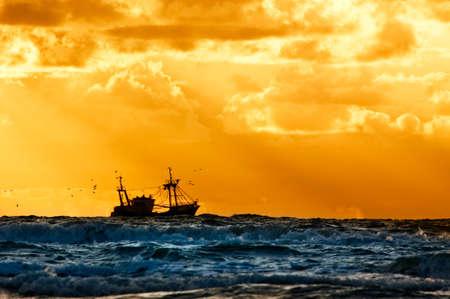 trawler: fishing ship at sea with sunset  Stock Photo