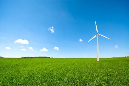 windmill with fresh green grass and clear blue sky in summer photo