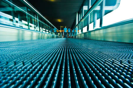 abstract image of people traveling on a moving escalator at airport taken with an ultra wide angle lens  photo