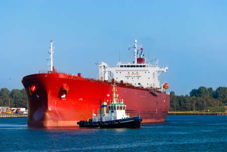 tugboat: A huge red oil tanker and a tugboat at work