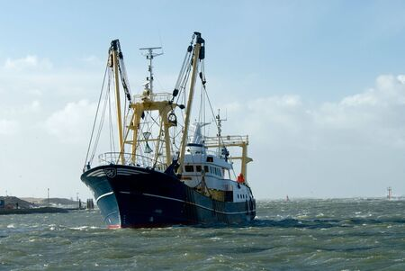 trawler: fishing ship during a storm in harbor  Stock Photo