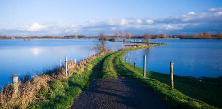 ijssel: a road into a flooded river (IJssel river Netherlands) Stock Photo