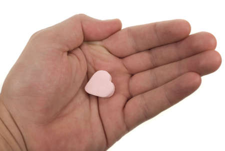 hand with heart shaped sweet isolated on a white background photo