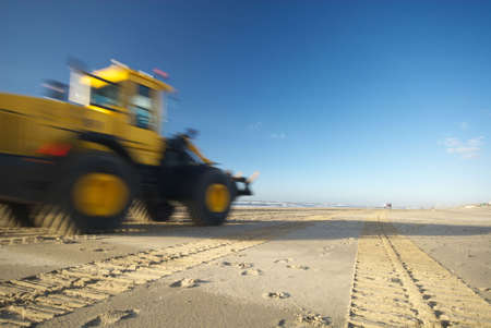 flatten: a bulldozer moving fast on the beach ( motion blur)