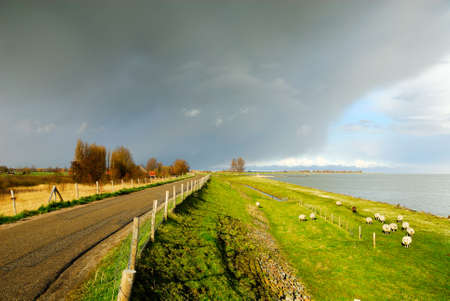 ijsselmeer: beautiful country road in the netherlands with a lake called the ijsselmeer to the right Stock Photo