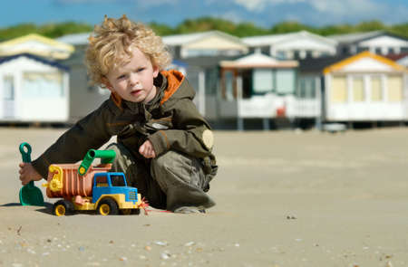 cute boy playing on the beach photo