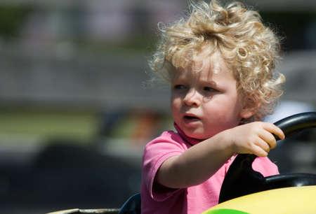 cute young boy having fun in yellow car